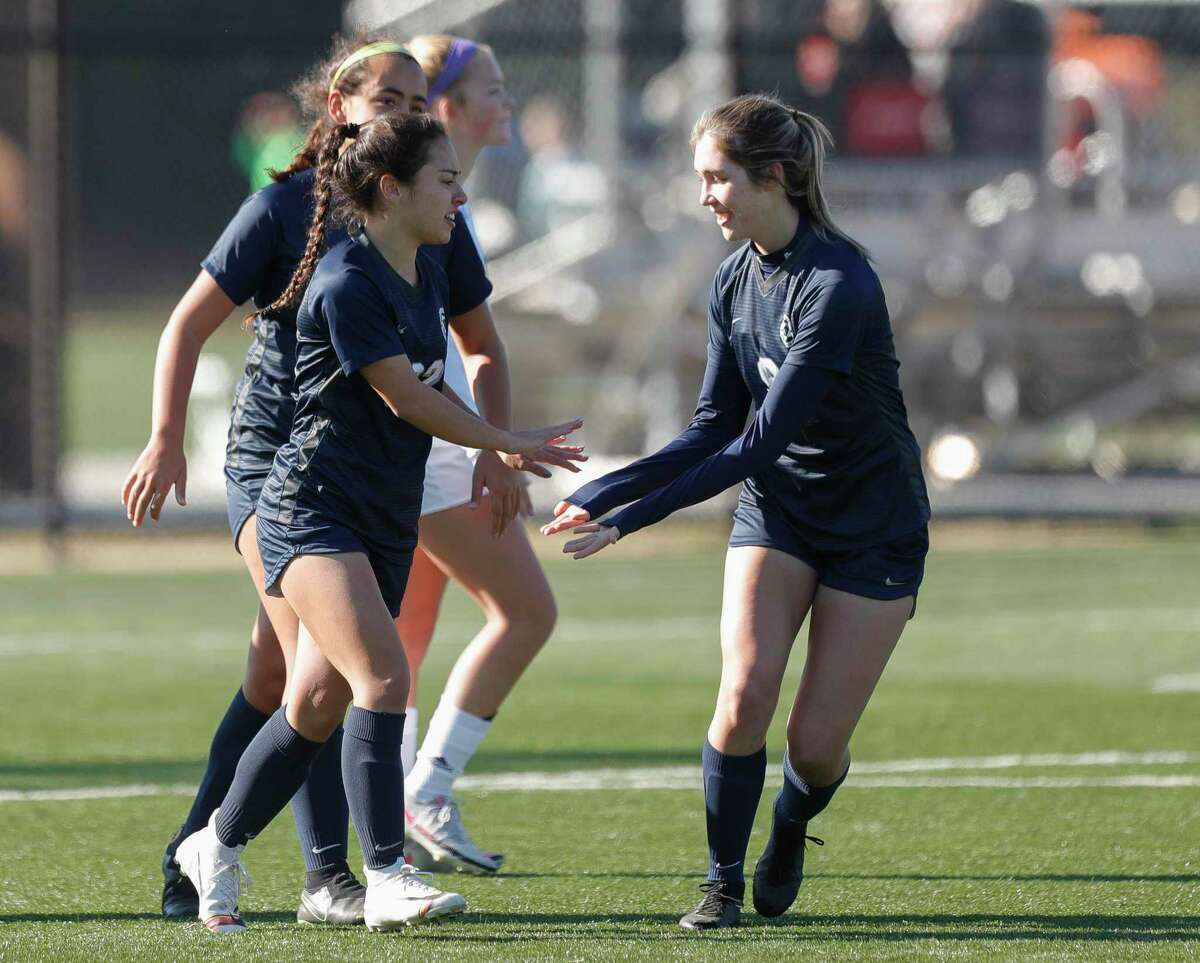 College Park's Mia Summers (22) gets a high-five from Sara Engels (9) after scoring a goal in the first period of a match during the Lady Highlander Invitational, Saturday, Jan. 9, 2021, in The Woodlands.