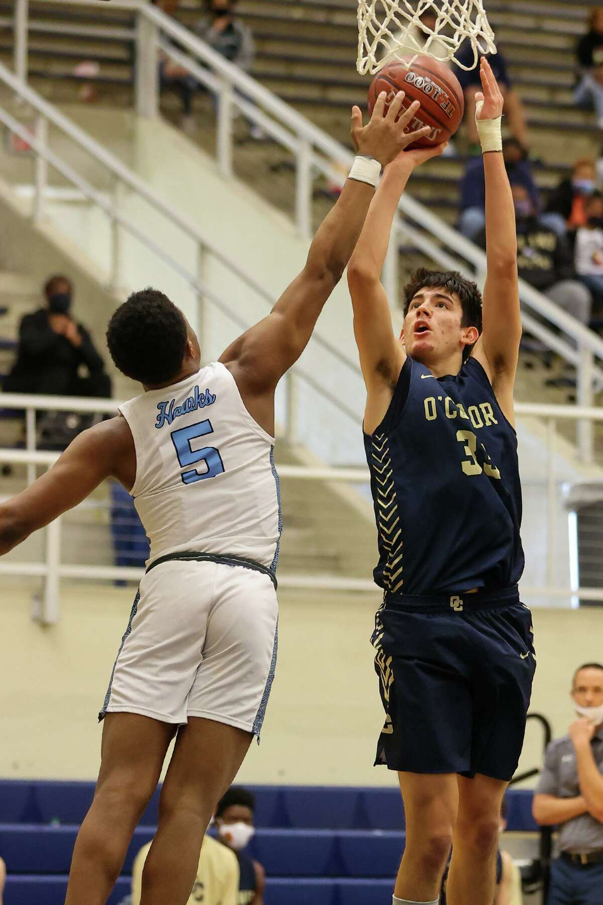 Harlan's Jaylen Streeter, left, tries to block a shot by O'Connor's Josh Alcocer during their District 29-6A boys basketball game at Paul Taylor Field House on Saturday, Jan. 9, 2021. O'Connor beat Harlan 59-50.