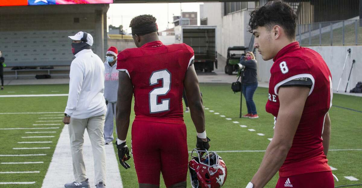 North Shore's Shadrach Banks (2) and David Amador (8) walk off the field after the Mustangs' 24-21 loss to Austin Westlake in the Class 6A Division I semifinal playoff high school football game at Legacy Stadium Saturday, Jan. 9, 2021 in Katy, Texas.