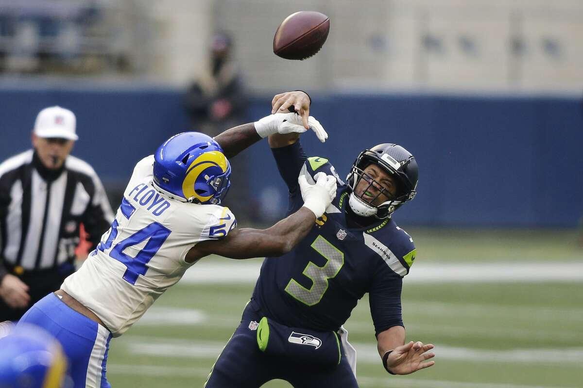 Rams linebacker Leonard Floyd, who had two of Los Angeles' five sacks, roughs up Seahawks quarterback Russell Wilson.