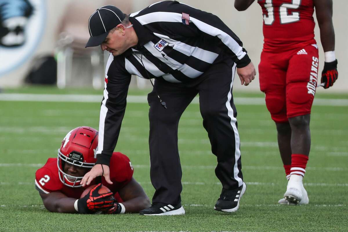 An official reaches down to grab the football as North Shore Shadrach Banks (2) lies on the field after coming up short on fourth down against Austin Westlake during the fourth quarter of a Class 6A Division I semifinal playoff high school football game at Legacy Stadium Saturday, Jan. 9, 2021 in Katy, Texas. Westlake advanced to the state title game with a 24-21 win.