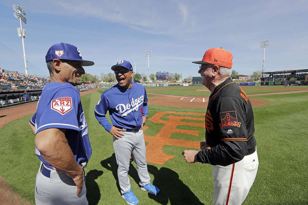 San Francisco Giants coach Joe Amalfitano, right, is greeted by Los Angeles Dodgers manager Dave Roberts, center, and third base coach Dino Ebel before a spring training baseball game Monday, March 4, 2019, in Scottsdale, Ariz. (AP Photo/Elaine Thompson)