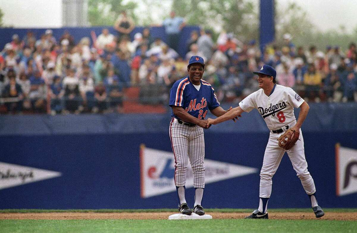 Hall of Famer Willie Mays, center, gets congratulations from former New York Giants player and current Los Angeles Dodgers coach Joe Amalfitano, after Mays hit a double in the Old Timers game between the Brooklyn Dodgers and New York Mets at Shea Stadium, Saturday, May 23, 1987, New York. (AP Photo/Susan Ragan)