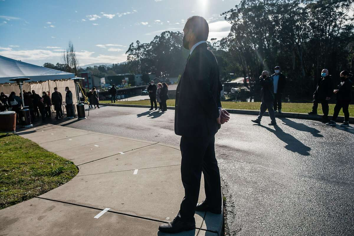 Assistant funeral director Dominic Blandino supervises an outdoor wake at Cypress Lawn Memorial Park in Colma. Bay Area funeral homes are struggling to keep up with demand as the pandemic's toll grows.