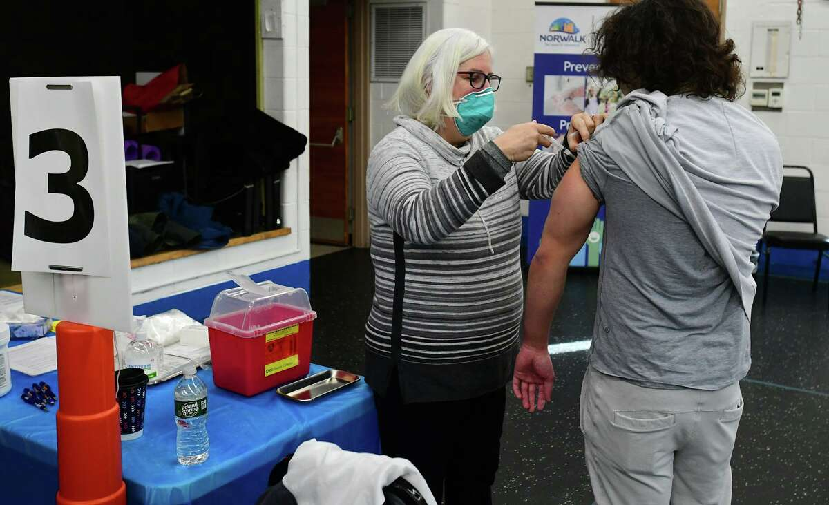A volunteer administers the new COVID vaccine in Norwalk in December.