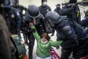 A woman is helped up by police during a rally Wednesday, Jan. 6, 2021, at the Capitol in Washington.