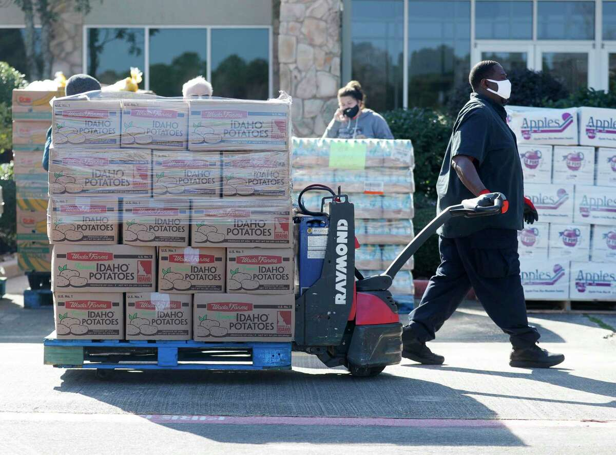 Kenny Miller helps move a pallet of supplies as volunteers distribute food for 200 families as part of YMCA's Mobile Market Food Drive in partnership with the Montgomery County Food Bank at Generations Church, Saturday, Jan. 9, 2021.
