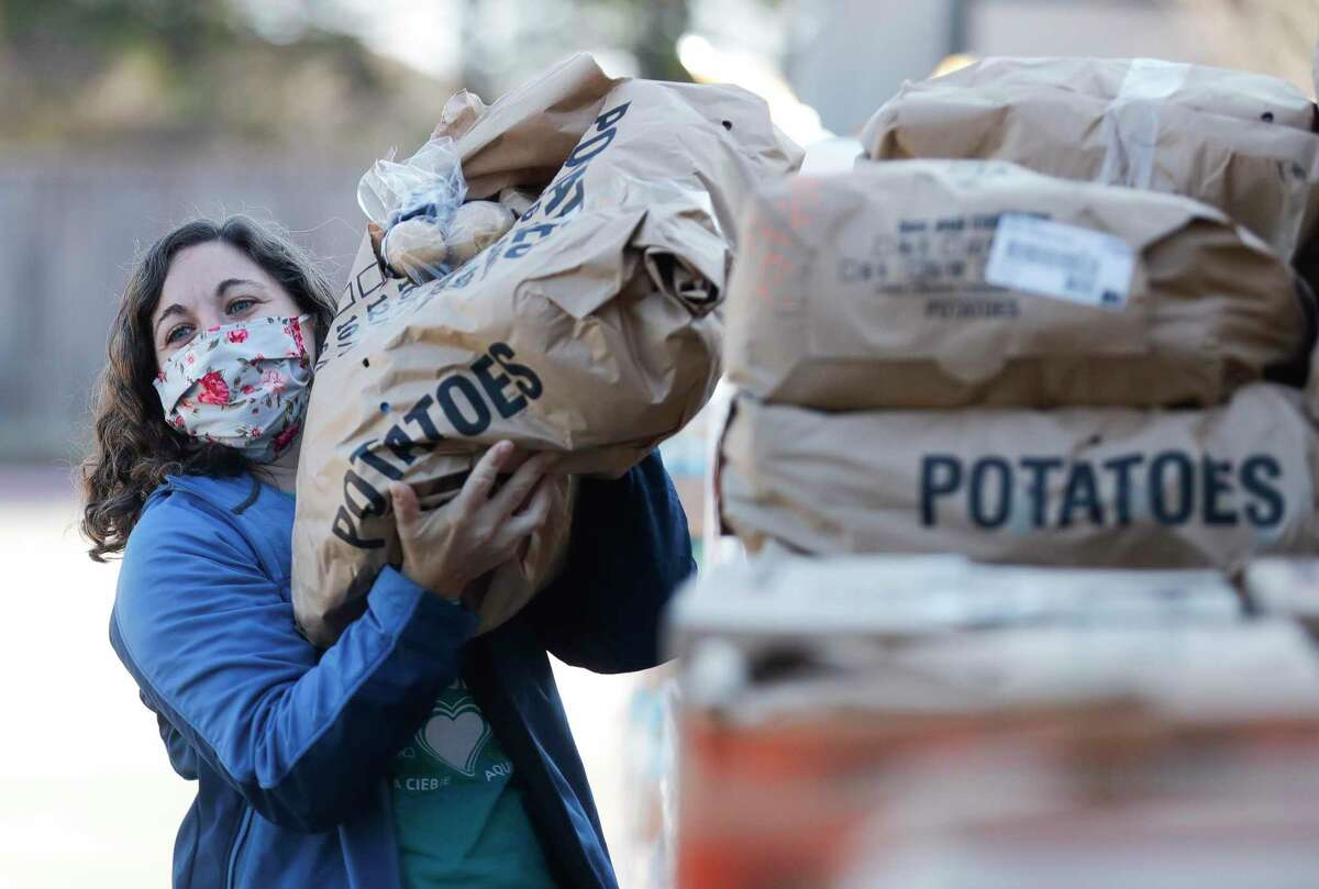 Whitney Vasquez moves a package of potatoes as volunteers help distribute food for 200 families as part of YMCA's Mobile Market Food Drive in partnership with the Montgomery County Food Bank at Generations Church, Saturday, Jan. 9, 2021.