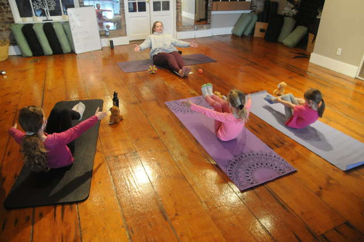 Instructor Kim Speidel puts young participants through their paces during Saturday's Kids Yoga class in Alton.