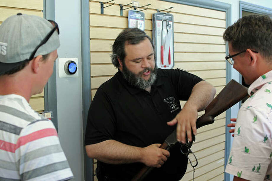 """In this June photo, Piasa Armory employee Jason Heeren demonstrates a shotgun for customers at the Alton business. Currently both firearms and ammunition are in short supply in the Riverbend area. """"All of the common stuff is just gone."""" — Scott Pulaski"""