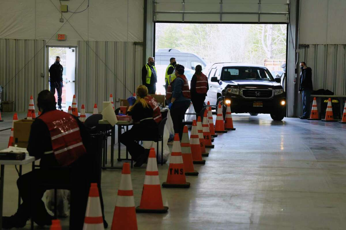 People showing up to be vaccinated drive their vehicles into a large garage at a pilot vaccination administered by the Albany County sheriff's department on Sunday, Jan. 10, 2021, in New Scotland, N.Y. In the first hour of the vaccination pod, over 70 people were vaccinated Sheriff Craig Apple said. The sheriff's department was given 216 vaccines for the pilot program. Sheriff Apple said that he is expecting to have between 800 and 1,000 vaccines for Tuesday. The sheriff also said that they are looking at ways to be able to set up vaccination pods at schools to vaccinate teachers. (Paul Buckowski/Times Union)