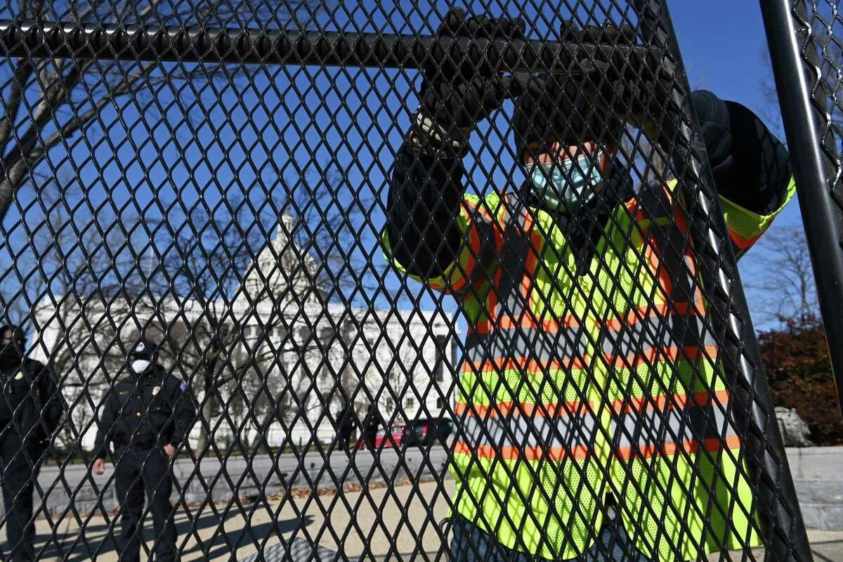 Workers put up fencing outside the U.S. Capitol on Jan. 7.