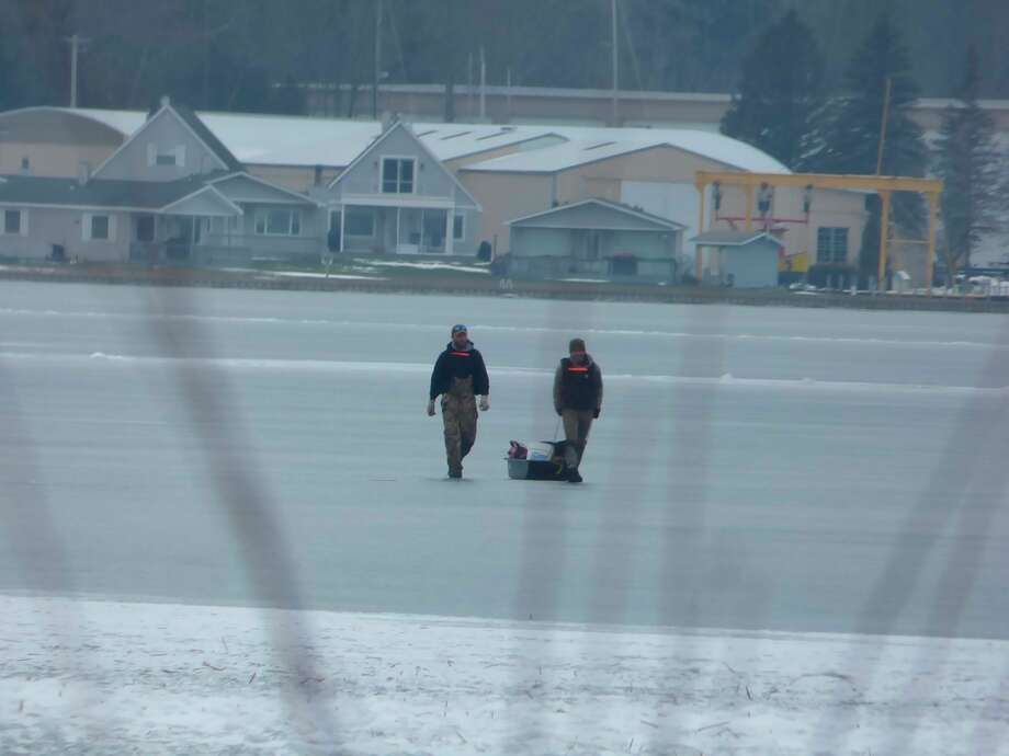 A pair of fishermen cross the ice on Portage Lake Sunday. (Scott Fraley/News Advocate)