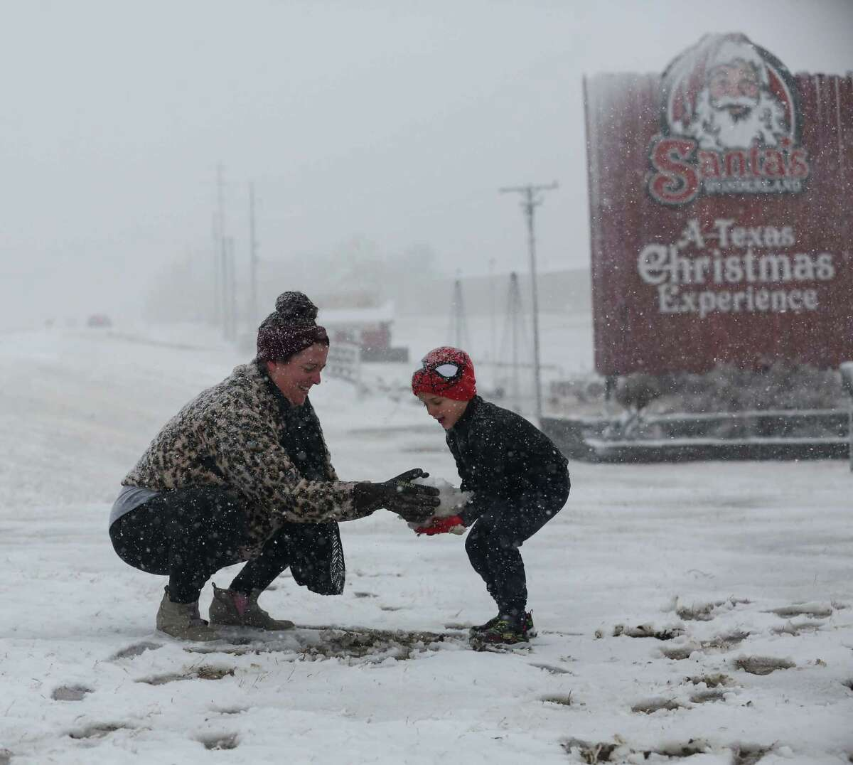 Heather makes a snow ball and hands it to her son, Weston, 5, to build a snowman at Santa's Wonderland on Highway 6 Sunday, Jan. 10, 2021, in College Station. The family of five drove up from Waller to find snow.
