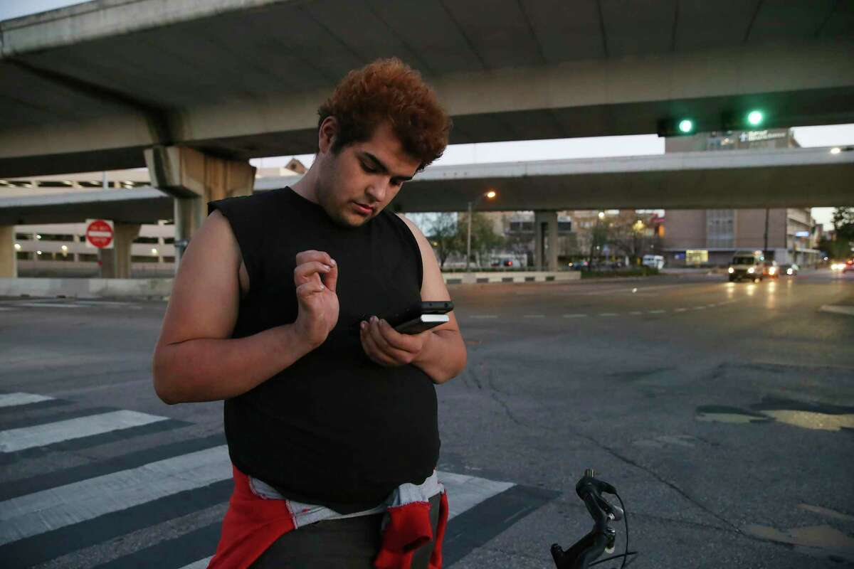 Isabella Cardenas, 22, texts with a friend after visiting her sister at a nearby motel near the corner of IH-35 and North Main Avenue, Wednesday, Jan. 6, 2021. Cardenas has been on the streets for a while and is now staying with friends in a tent under IH-37. San Antonio Regional Alliance for the Homeless, (SARAH), is partnering with five agencies to help area homeless youth through an almost $5 million grant to provide various programs, such as rapid rehousing, transitional housing and mobile outreach.