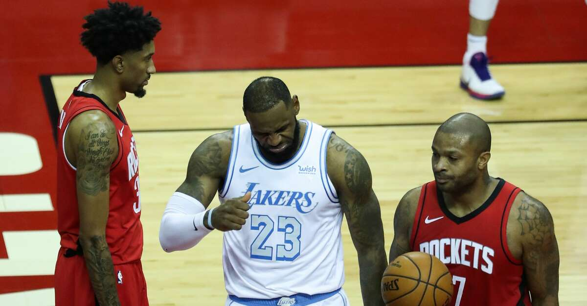 Los Angeles Lakers forward LeBron James (23) reacts after scoring on a layup against Houston Rockets center Christian Wood (35) and forward P.J. Tucker (17) during the second quarter of an NBA basketball game on Sunday, Jan. 10, 2021, at Toyota Center in Houston.
