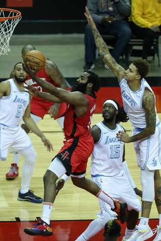 Houston Rockets guard James Harden (13) drives to the basket past Los Angeles Lakers center Montrezl Harrell (15) and forward Kyle Kuzma (0) during the third quarter of an NBA basketball game on Sunday, Jan. 10, 2021, at Toyota Center in Houston. Photo: Brett Coomer/Staff Photographer / © 2021 Houston Chronicle