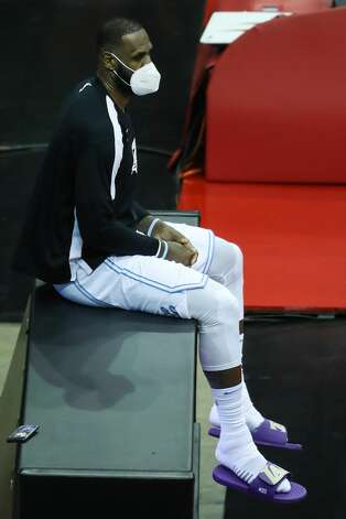Los Angeles Lakers forward LeBron James sits on one of the advertising boards after leaving the game against the Houston Rockets during the fourth quarter of an NBA basketball game on Sunday, Jan. 10, 2021, at Toyota Center in Houston. The Lakers beat the Rockets 120-102. Photo: Brett Coomer/Staff Photographer / © 2021 Houston Chronicle