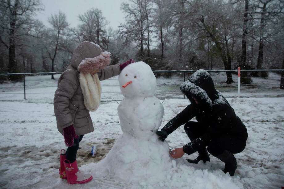 Camila Sustaita, 7, builds a snowman with stepmother, Jay Denise Morales, Sunday in College Station. It took four people an hour to build this snowman. Photo: Yi-Chin Lee, Houston Chronicle / Staff Photographer / © 2021 Houston Chronicle