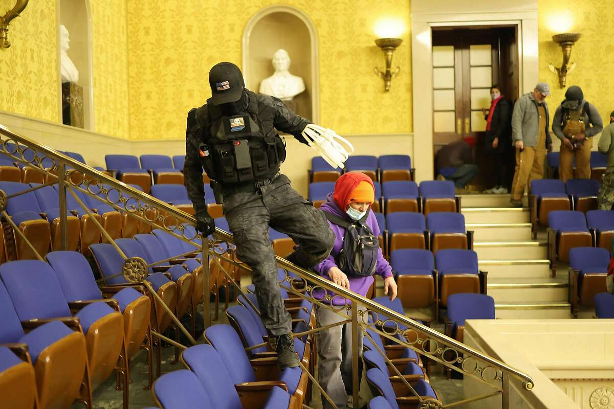 Protesters enter the Senate Chamber on Jan. 6, 2021 in Washington, D.C. Two men photographed carrying zip-ties in the U.S. Capitol Wednesday were charged Sunday in a federal court in the District of Columbia. (Win McNamee/Getty Images)