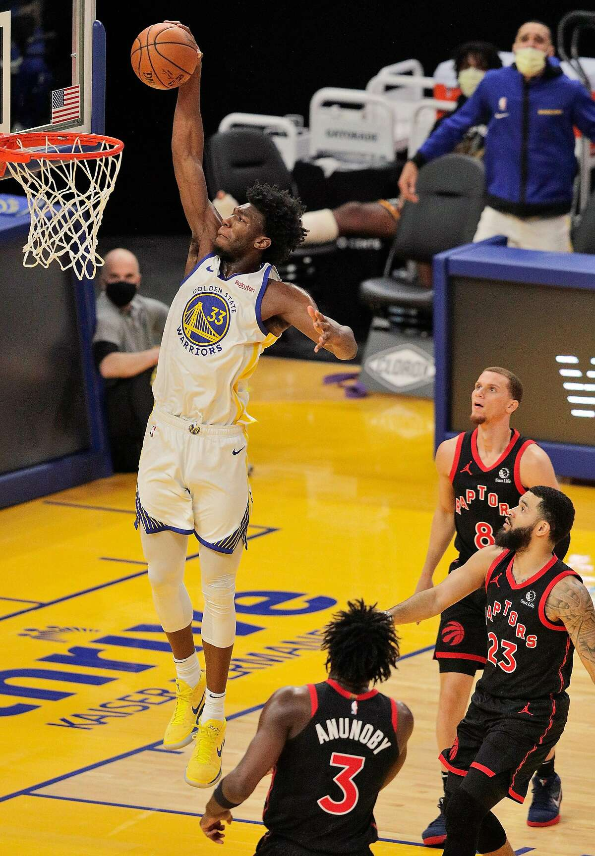 The Warriors' James Wiseman, a rookie center rising quickly, rises up high to dunk over three Raptors in the first half.