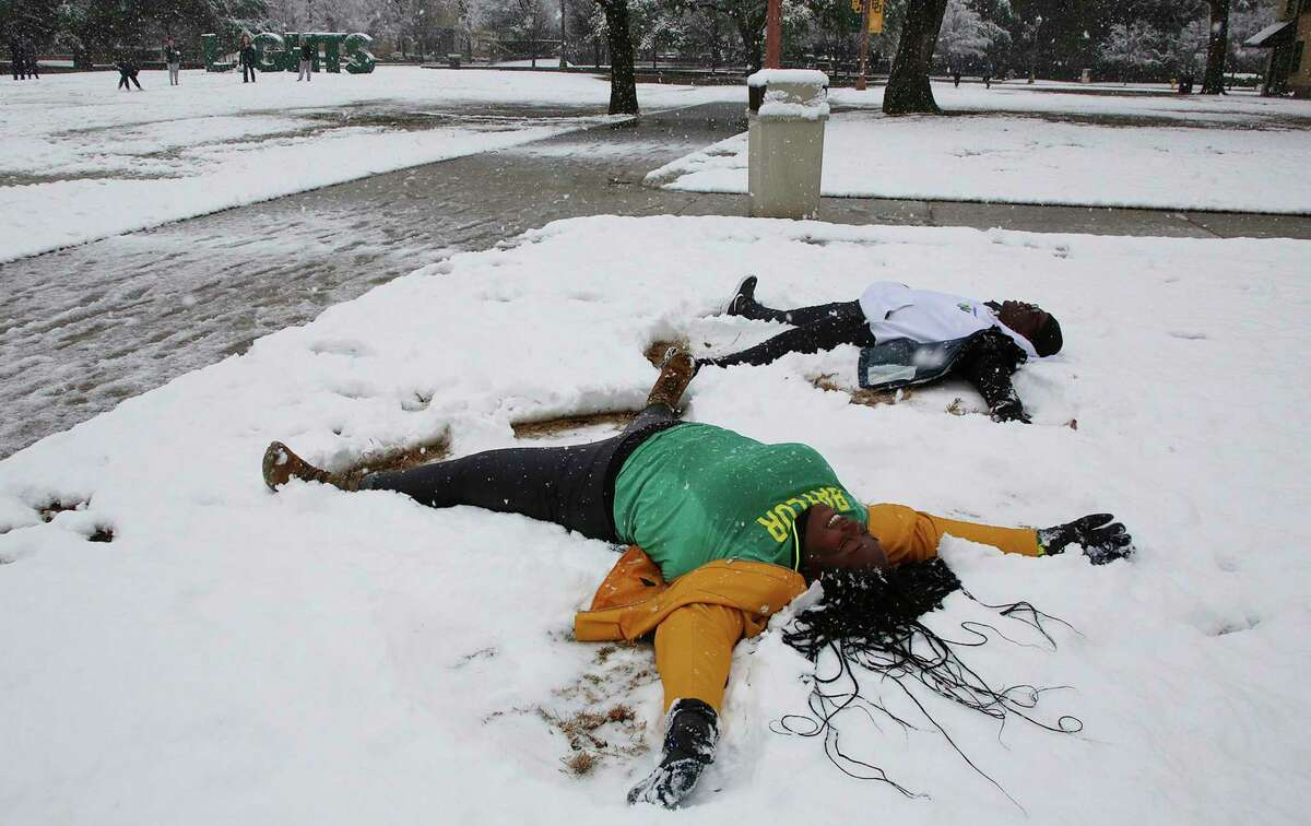 Baylor University students make snow angels after at least five inches were reported throughout Central Texas Sunday, Jan. 10, 2021, in Waco, Texas. ( (Rod Aydelotte/Waco Tribune-Herald via AP)
