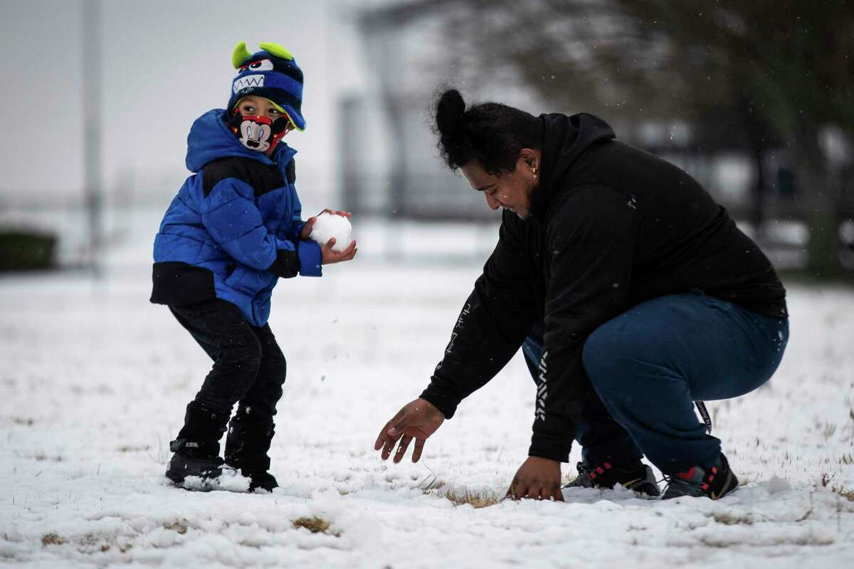 Jonathan Godoy, 5, looks for a target as Elias Gonzales makes a new snowball Sunday, Jan. 10, 2021, near Benbrook Community Center. National Weather Service in Fort Worth predicted 1 inch to 2 inches of snow will fall in Tarrant and Dallas counties over the course of the day. (Yffy Yossifor/Star-Telegram via AP)