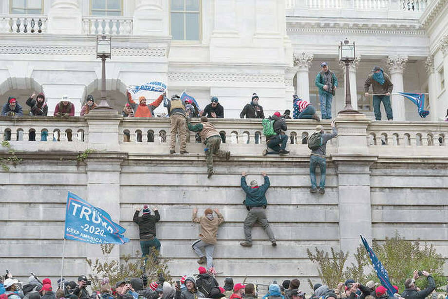 Rioters climb the west wall of the Capitol in Washington. Photo: Jose Luis Magana | AP