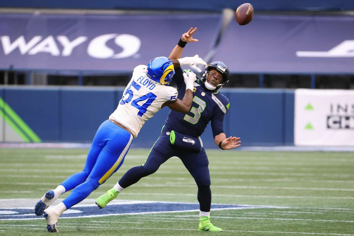 SEATTLE, WASHINGTON - JANUARY 09: Russell Wilson #3 of the Seattle Seahawks throws an incomplete pass while being hit by Leonard Floyd #54 of the Los Angeles Rams in the second quarter during the NFC Wild Card Playoff game at Lumen Field on January 09, 2021 in Seattle, Washington. (Photo by Abbie Parr/Getty Images)