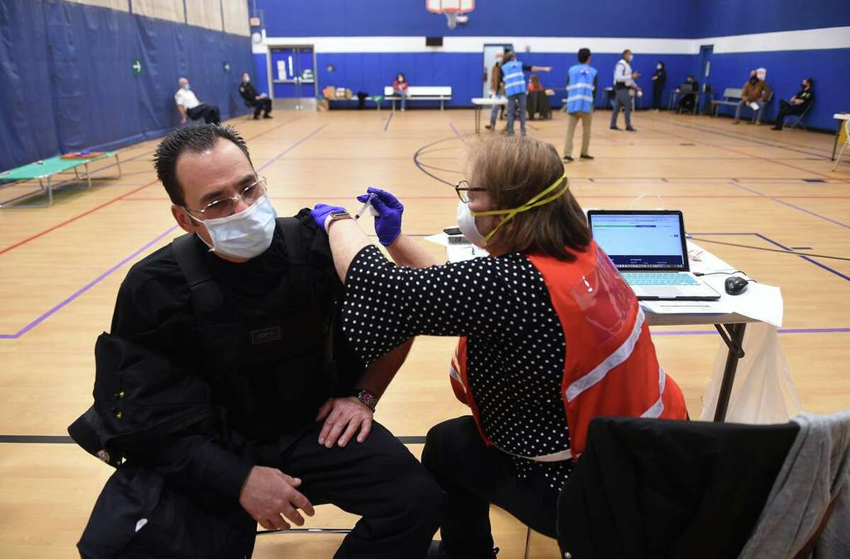 Madison Police Officer John Palmer (left) gets a dose of the Moderna COVID-19 vaccine by RN Maureen Spinnato at the Madison Town Campus gymnasium on January 6, 2021. The East Shore District Health Department along with the Madison and Guilford Health Departments vaccinated 130 EMS and first responders from the towns of Madison, Guilford, Branford, North Branford and East Haven Wednesday following the vaccination of 200 the previous week.