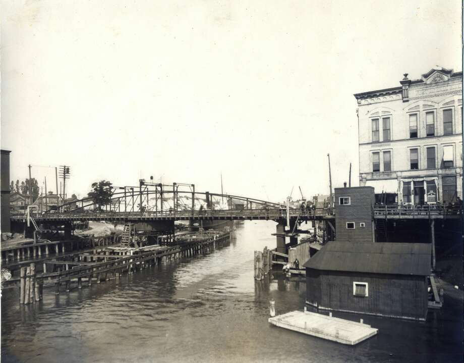 A view from the Manistee River Channel looking east with the Maple Street Bridge and the first Engelmann Block in sight 1904. Photo: Manistee County Historical Museum / Copyright 2020, Manistee County Historical Society, Inc.
