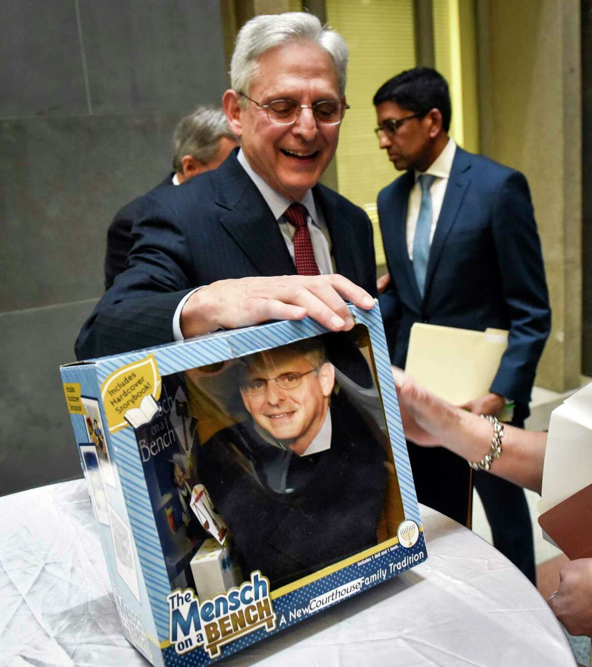 Judge Merrick Garland studies a toy that has been customized with his likeness, during a February, 2020 ceremony to pass the title of chief judge of the U.S. Court of Appeals for the D.C. Circuit to Sri Srinivasan, back right.