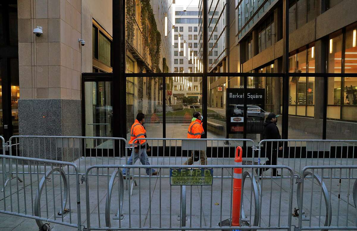 Pedestrians walks by Market Square near Twitter headquarters behind barricades placed in anticipation of supporters of President Donald Trump protesting outside later during a planned gathering in San Francisco, Calif., on Monday, January 11, 2021. The social media company suspended the president earlier in the week following the violent takeover of The United States Capitol last week by his supporters.