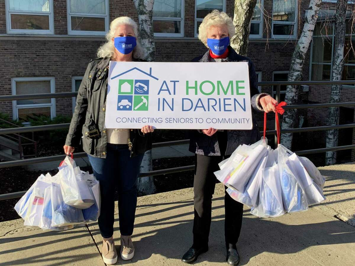 At Home In Darien Board Members Monica Billeter and Robin Woods prepare to deliver gift bags to residents of The Royle.