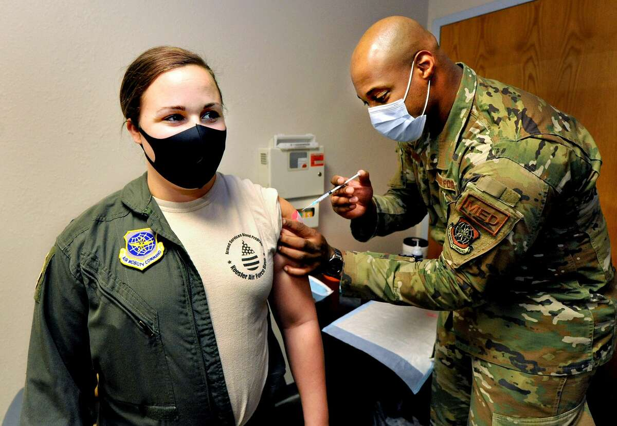 Capt. Kayla Pounds of Brownsburg, Indiana (left) receives her first dose of Covid-19 vaccine from Staff Sgt. And medic Gibbs Bellamour of Philadelphia at Scott Airforce Base Friday.
