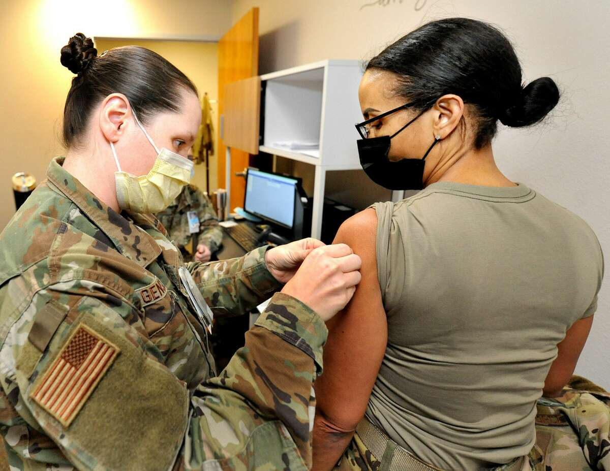 Medic and Tech Sgt. Rebecca Genslanger of Payson, Il. (left) puts a band aid on Capt. Jennifer Wilcox of Colorado Springs, Colorado after vaccinating her with the Covid-19 vaccine Friday at Scott Airforce Base.