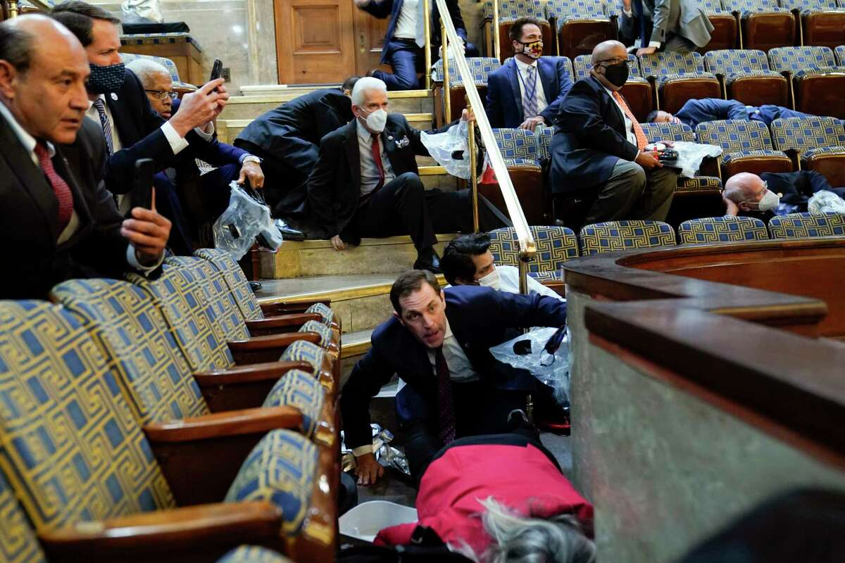 People shelter in the House gallery as protesters try to break into the House Chamber at the U.S. Capitol on Wednesday, Jan. 6, 2021, in Washington. (AP Photo/Andrew Harnik)