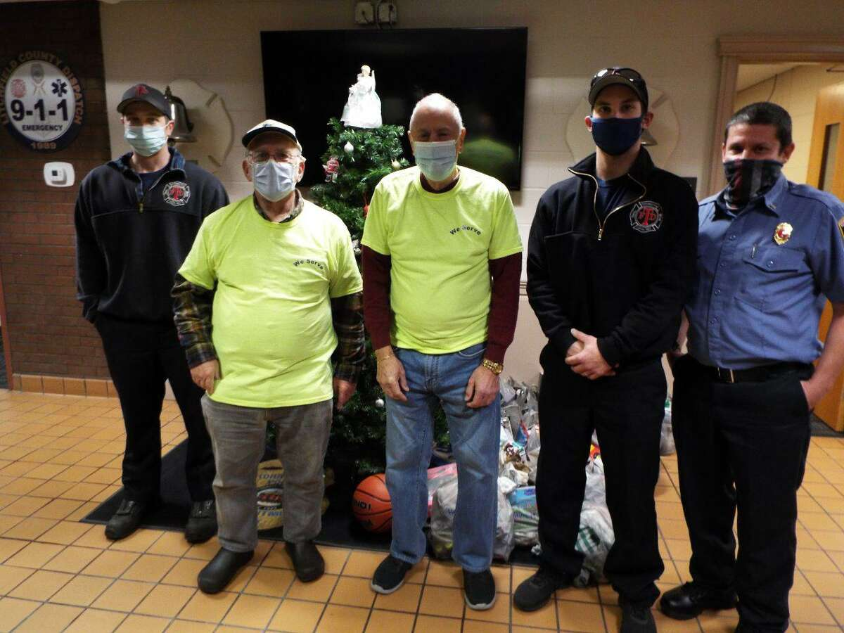 Club members Norm NeJaime and Phil Dzurnak presented a donation of gifts to three members of the fire department.