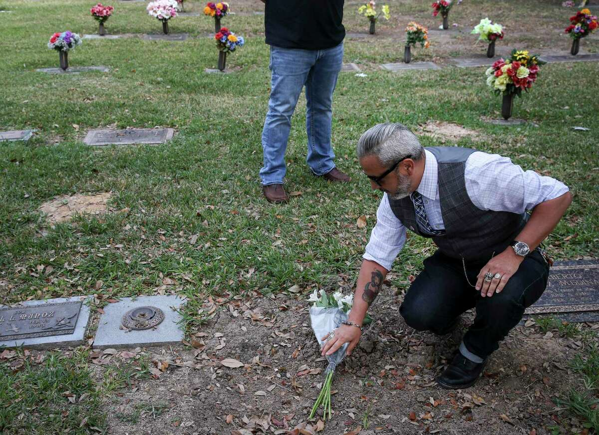 Paul De La Cerda puts flowers on his father's gravesite as his brother Michael, rear, watches Thursday, Nov. 26, 2020, at Forest Lawn Cemetery in Houston. Their father, a professional limousine driver, died in July after battling COVID-19.