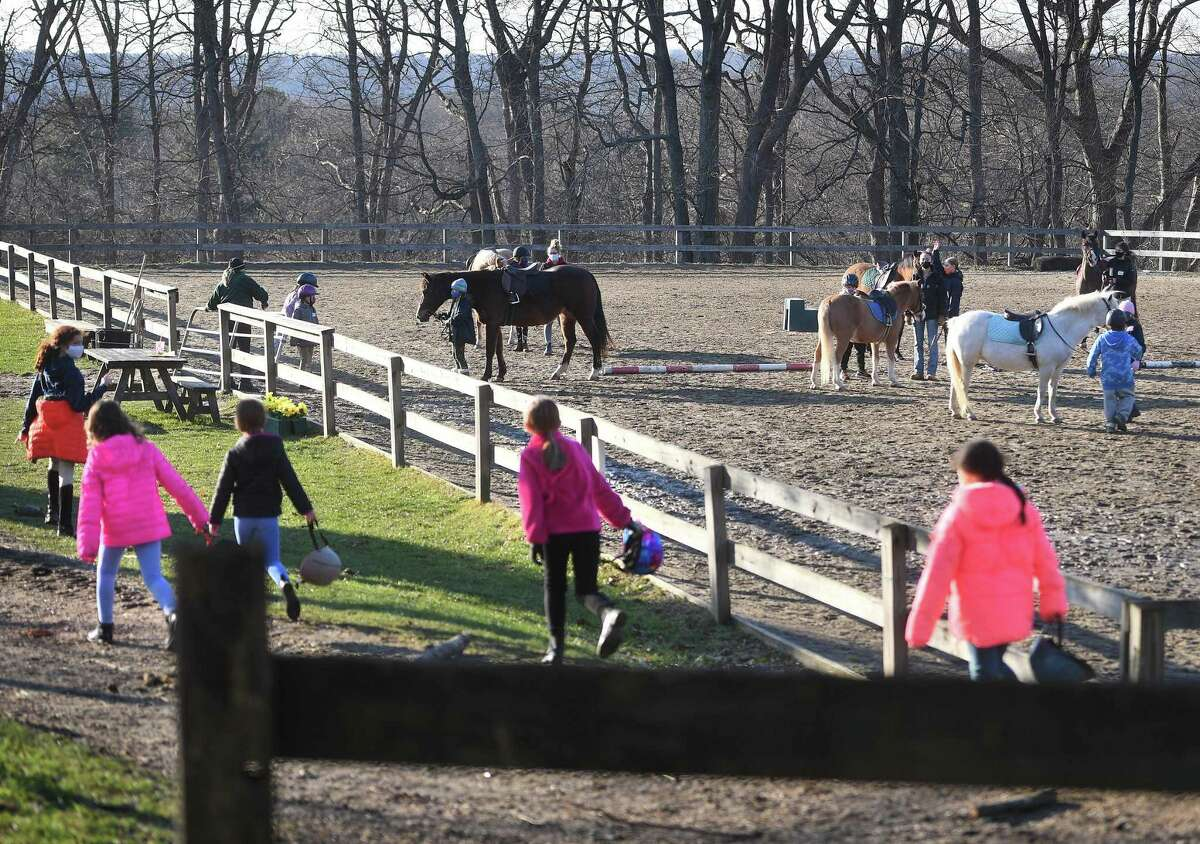 Socially distanced campers head for the riding ring during the first annual Chester Hill Farm Winter Camp at the riding stable in Trumbull, Conn. on Monday, December 28, 2020.