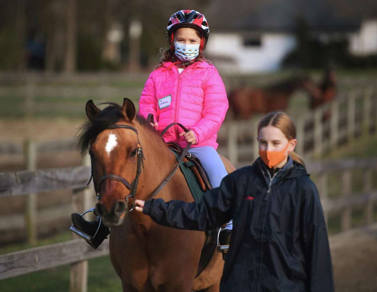 Broken up into socially distanced groups, campers learn the joys of horeseback riding during the first annual Chester Hill Farm Winter Camp at the riding stable in Trumbull, Conn. on Monday, December 28, 2020.