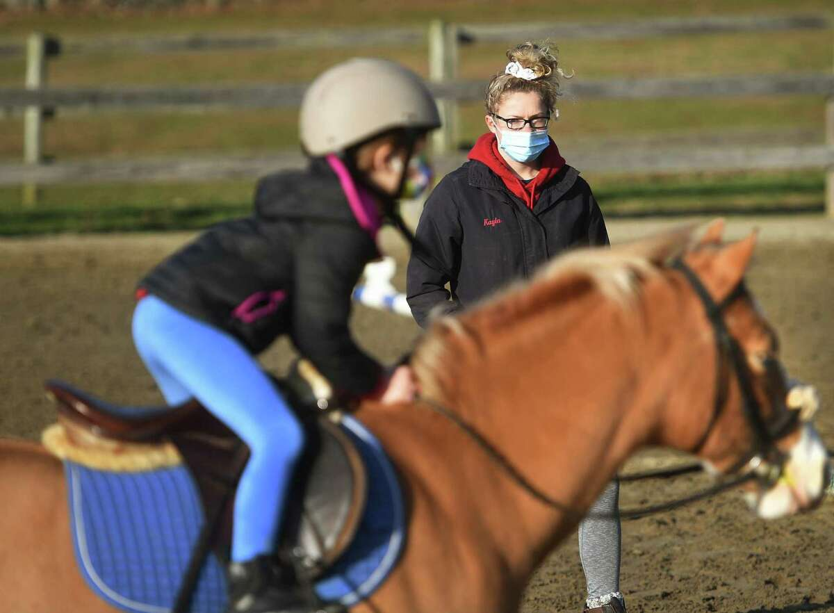 Kayla Dalling, of Stratford, guides young riders in horseback riding instruction during the first annual Chester Hill Farm Winter Camp at the riding stable in Trumbull, Conn. on Monday, December 28, 2020.