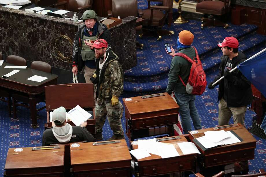 Retired Air Force Lt. Col. Larry Brock from Texas, seen in the green helmet in the Senate Chamber on Jan. 6, was arrested after being reported to the FBI for his role in the Capitol riot. (Photo by Win McNamee/Getty Images)(Photo by Win McNamee/Getty Images) Photo: Win McNamee/Getty Images / 2021 Getty Images