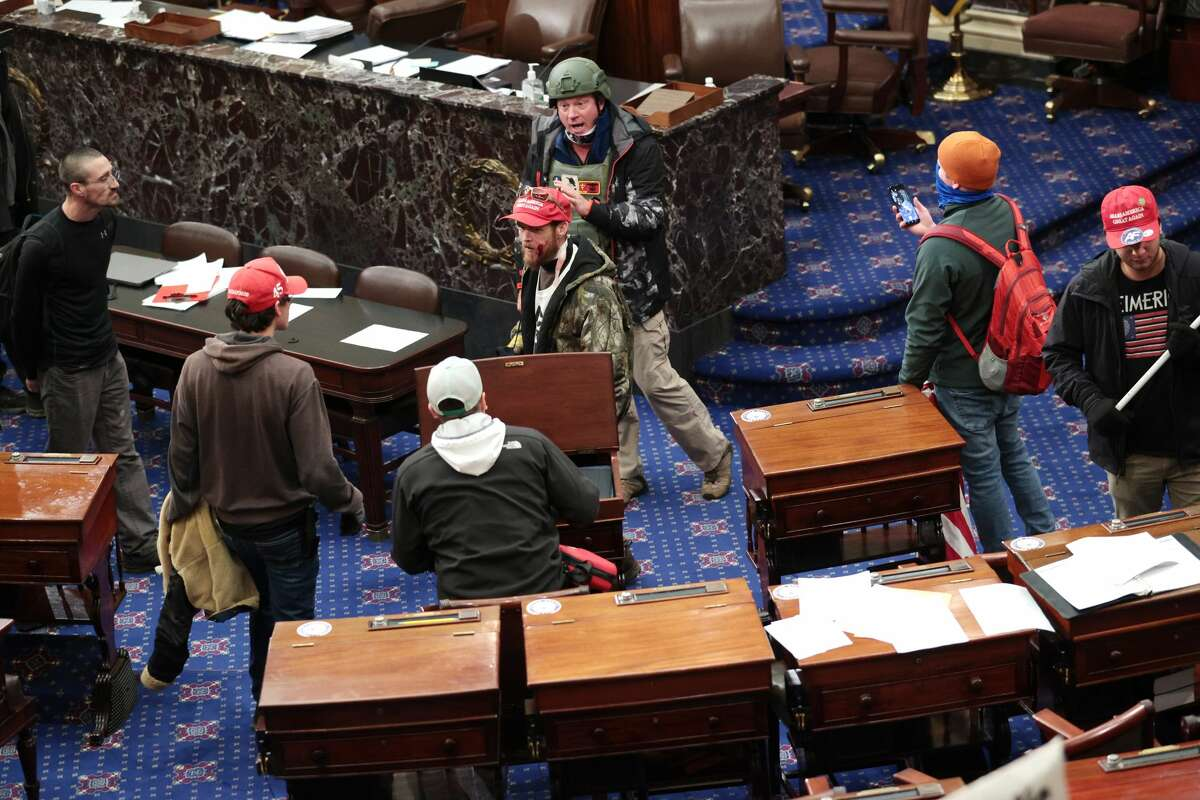 Retired Air Force Lt. Col. Larry Brock from Texas, seen in the green helmet in the Senate Chamber on Jan. 6, was arrested after being reported to the FBI for his role in the Capitol riot. (Photo by Win McNamee/Getty Images)(Photo by Win McNamee/Getty Images)