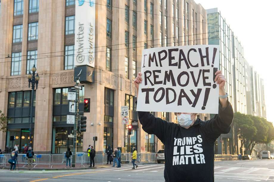 A man carries a sign across the street from the Twitter headquarters on Monday, January 11, 2021. Photo: Blair Heagerty/SFGATE