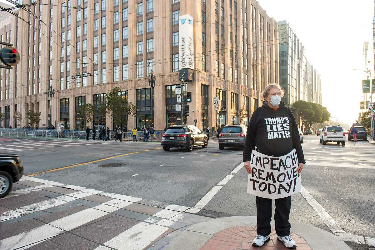 A man carries a sign across the street from the Twitter headquarters on Monday, January 11, 2021.
