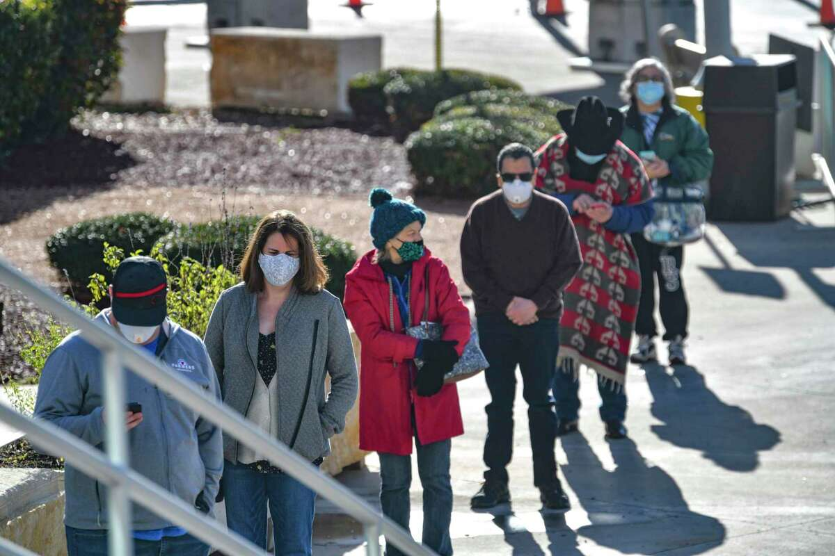 People arrive for their no-cost COVID-19 vaccinations at the Alamodome on Monday, Jan. 11, 2021. About 9,000 vaccines will be given at the site this week, or about 1,500 per day, depending on staffing.