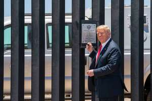 President Donald Trump signs a portion of his border wall in Arizona this summer. The wall is a monument to failure, built on the president's falsehoods.