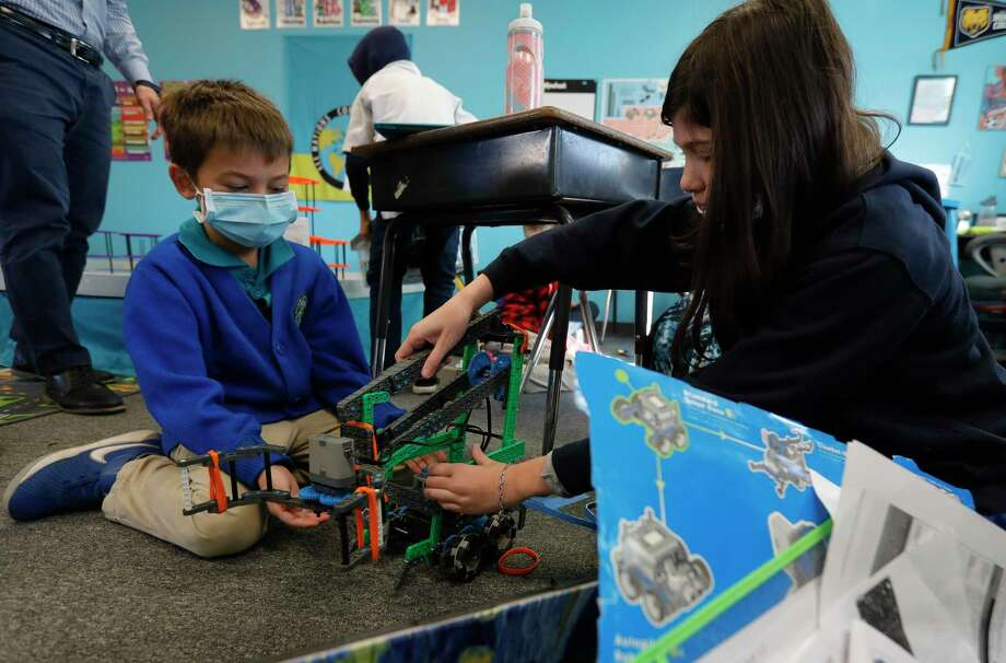 Isaac Wolfard, left, helps set up a robot with Elena Welty during class, Thursday, Jan. 7, 2021. All Nations Community School is partnering with Journey School for the Uniquely Gifted and Talented for a joint after school robotics program. Photo: Jason Fochtman, Houston Chronicle / Staff Photographer / 2021 © Houston Chronicle