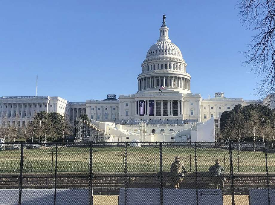 Members of the National Guard stand inside anti-scaling fencing that surrounds the Capitol, Sunday, Jan. 10, 2021, in Washington. The inaugural stand is center.  (AP Photo/Alan Fram) Photo: Alan Fram, Associated Press
